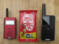 Tiny CP183 and CP228 walkie-talkies next to a KitKat bar